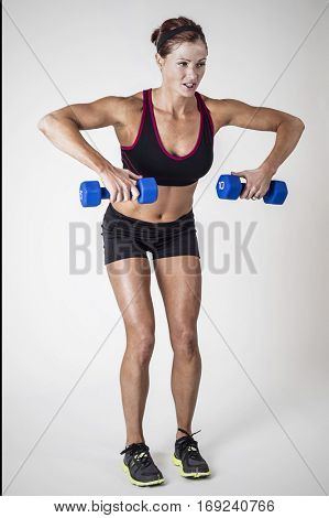 Beautiful strong muscular woman lifting dumbbell free weights in an indoor gym. Serious Female body builder doing bicep curls workout full length