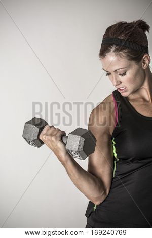 Beautiful strong muscular woman lifting dumbbell free weights in an indoor gym. Serious Female body builder doing a crossfire workout
