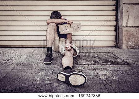 Hungry, homeless man begging on street of French city, holding 'J'ai faim' - I am hungry - sign