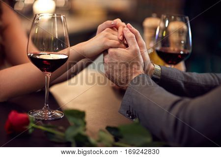 Close up of couple hold hands in pub-concept
