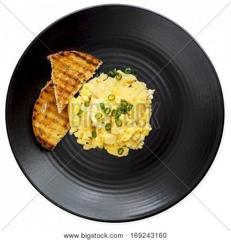 Scrambled eggs and toast on black plate.  Top view, isolated on white.
