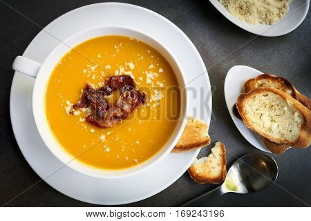 Pumpkin soup with bacon, parmesan and garlic bread.  Top view, over dark slate.