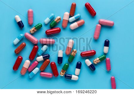 Different multicolored pills and medicine capsules on blue background