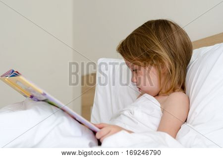 Cute little girl reading book in bed.