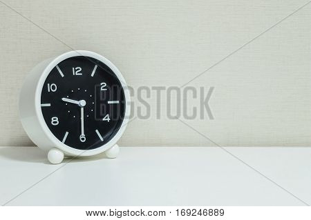 Closeup black and white alarm clock for decorate show show half past nine or 9:30 a.m. on white wood desk and cream wallpaper textured background with copy space