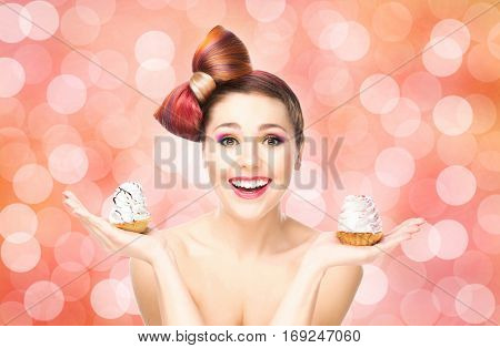 Beautiful woman with a bow haircut holding a cake on bubbly background.