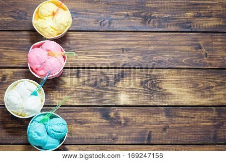 Top view of colored ice crem in cups on wooden rustic background