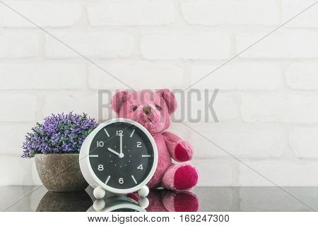 Closeup black and white alarm clock for decorate in 10 o'clock with bear doll and plant on black glass table and white brick wall textured background with copy space