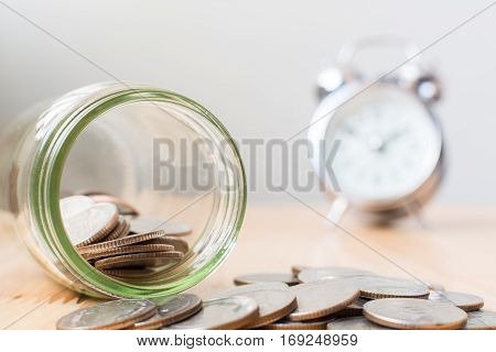 Concept saving money business finance for investment Coins in glass with clock