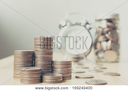 Concept business finance save money Coins stack on wood table with blurred alarm clock and money in jar