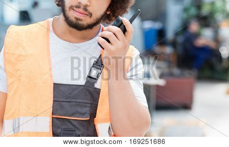 Young manual worker listening to walkie-talkie while looking up in metal industry