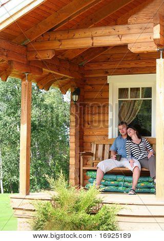 young couple drinking tea on veranda