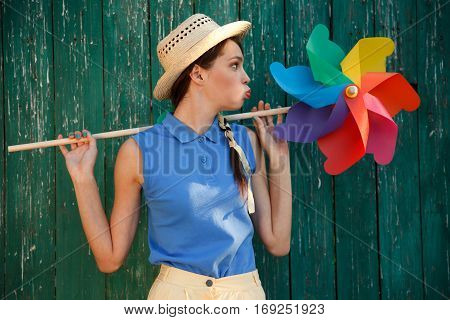 Young happy funny (vintage) dressed woman with colorful weather vanelooking like flower. Old green fence on the background. Picture ideal for illustating woman magazines.