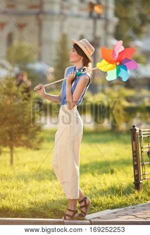 Young happy funny (vintage) dressed woman with colorful weather vane,looking like flower  Picture ideal for illustating woman magazines.