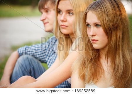 Three teenagers portrait with focus on the foreground on one girl and other teens out of focus
