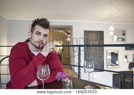 Portrait of confident young man drinking water from glass in cafe