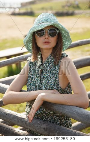 oung girl in strow hat and romantic style dress stands near wood fence outdoors in countryside. Professional style and make-up