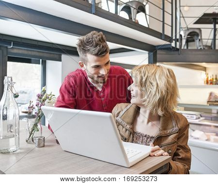 Young couple looking at each other while using laptop in cafe
