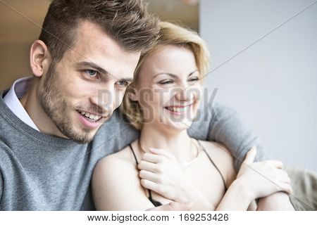 Happy young couple looking away in cafe