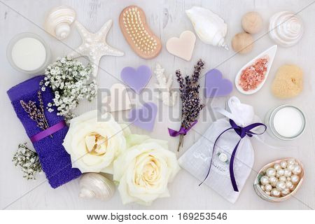 Lavender and rose flowers with spa and bathroom accessories with himalayan salt, soap, bath bombs, face towel, sponge, moisturising cream and decorative shells and pearls.