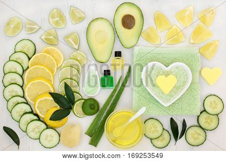 Ingredients for skin care beauty treatment with cucumber, aloe vera, avocado and citrus fruit with essential oil, exfoliating salt and flannels on distressed white wood background.