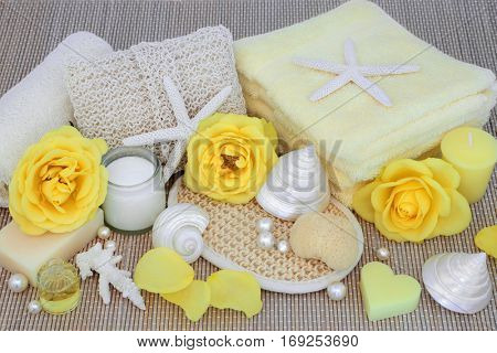Natural spa beauty treatment products with yellow rose flowers, shells and pearls on bamboo background.