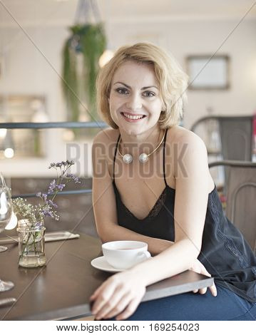 Portrait of happy young woman sitting at restaurant table