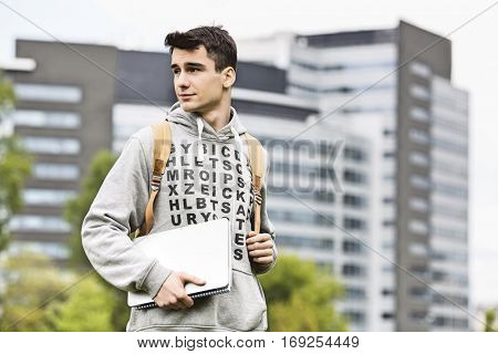Young male university student holding books at campus