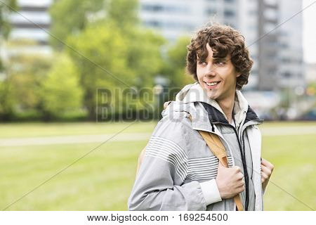 Smiling young male university student at college campus