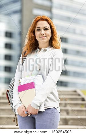 Portrait of beautiful young woman with textbooks at college campus