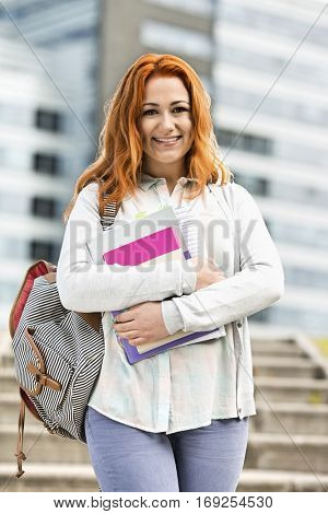 Portrait of beautiful student with textbooks at college campus