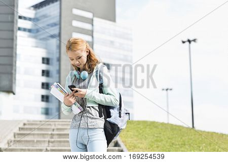 Young woman using smart phone at college campus