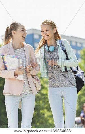 Cheerful young female college students walking in campus
