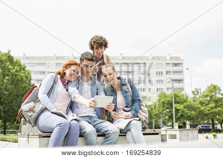 Young students photographing themselves through digital tablet at college campus