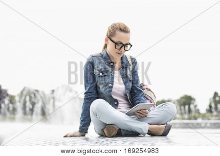 Full length of young female college student using digital tablet in park
