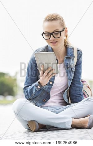 Full length of young female college student using tablet PC in park