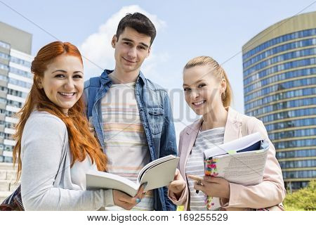 Portrait of happy young university students studying outdoors