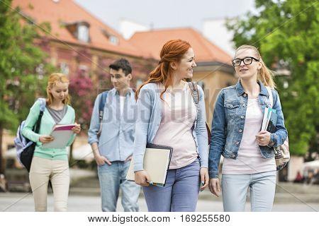 Young university friends walking on street
