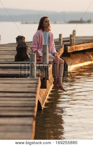 Young girl dressed in romantic style sits on old wooden pier with a dog on sunset. Professional style and make-up