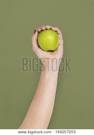 hand holding a green apple green background