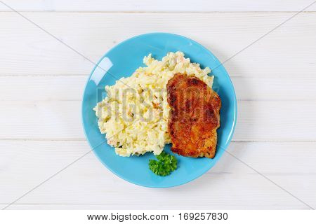 roasted chicken with potato salad on turquoise plate