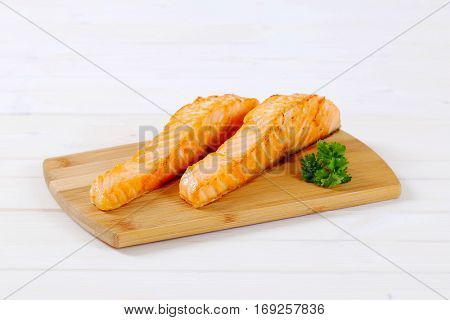 roasted salmon fillets on wooden cutting board
