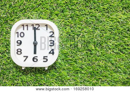 Closeup white clock for decorate in 6 o'clock on green artificial grass floor textured background with copy space