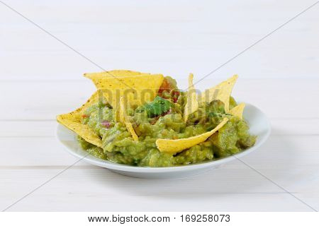 plate of guacamole with corn tortilla chips on white background