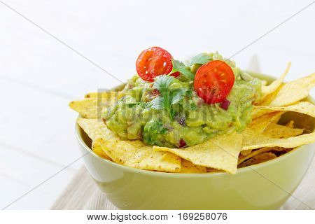 bowl of corn tortilla chips with guacamole dip - close up