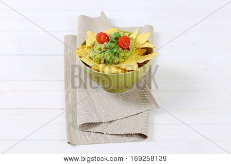 bowl of corn tortilla chips with guacamole dip on beige place mat