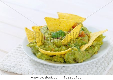 plate of guacamole with corn tortilla chips on white table mat - close up
