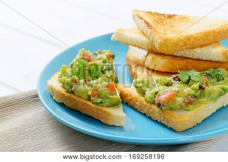 plate of toast bread with guacamole on beige place mat - close up