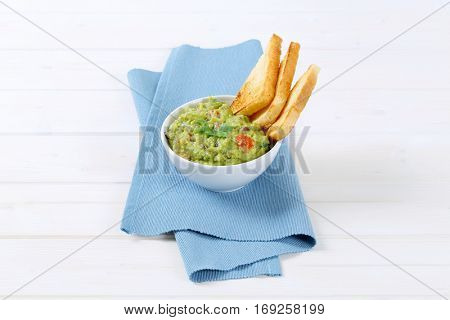 bowl of guacamole with toast bread on blue place mat