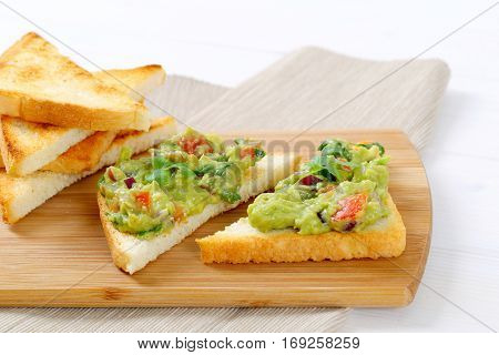toast bread with guacamole on wooden cutting board - close up